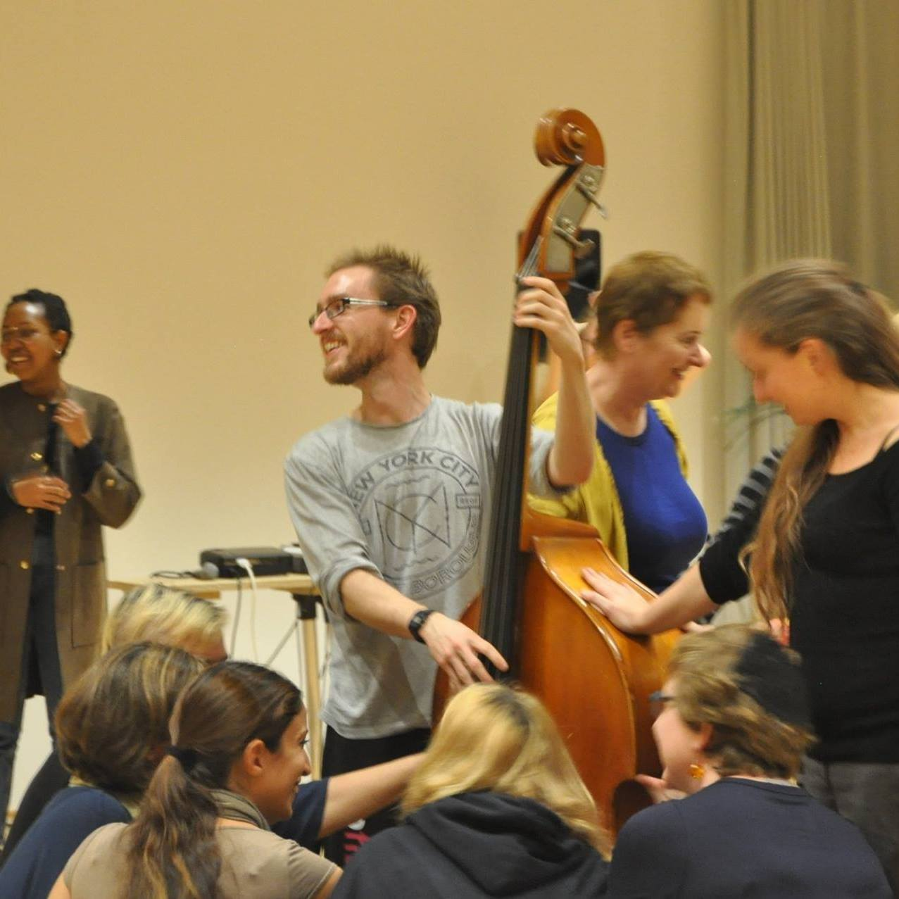 Doug Kemp playing double bass in a crowd, smiling